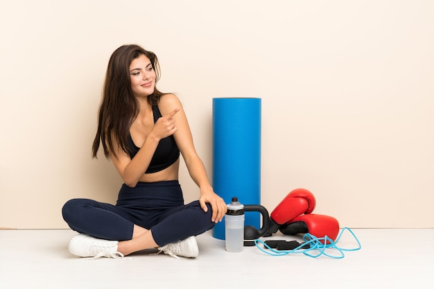 Teenager sport girl sitting on the floor pointing to the side to present a product