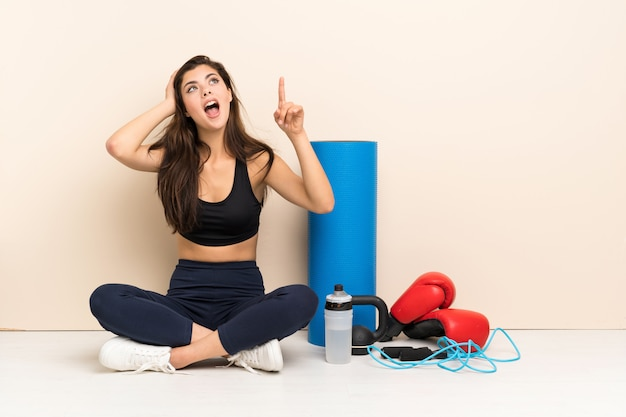Teenager sport girl sitting on the floor pointing up and surprised