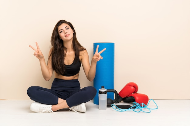 Teenager sport girl sitting on the floor showing victory sign with both hands