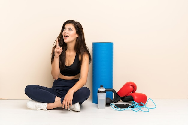 Teenager sport girl sitting on the floor thinking an idea pointing the finger up