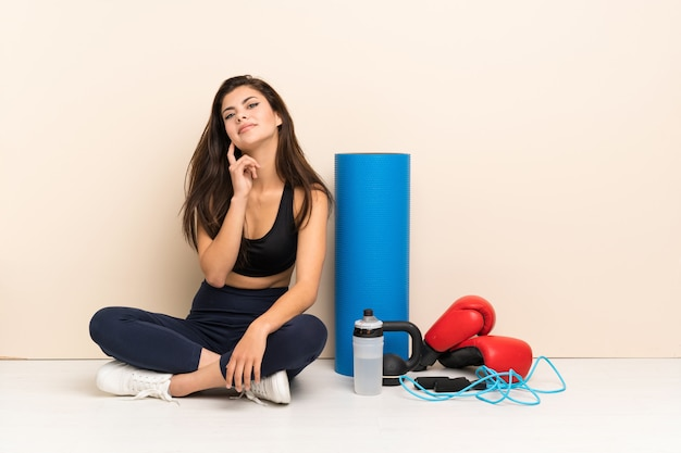 Teenager sport girl sitting on the floor thinking an idea while looking up