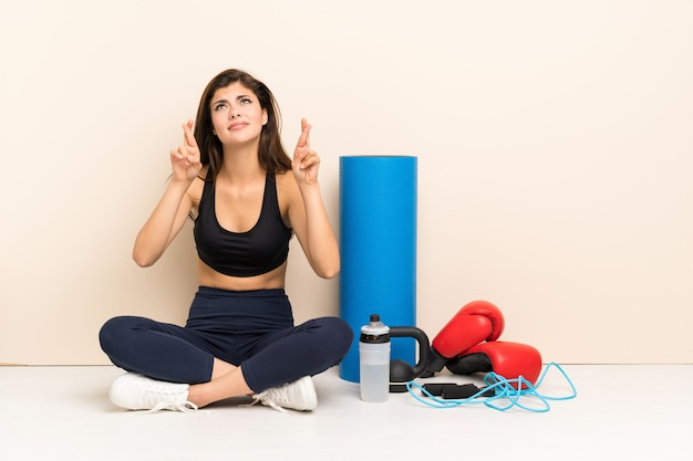 Teenager sport girl sitting on the floor with fingers crossing and wishing the best