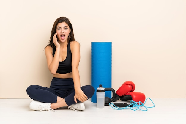Teenager sport girl sitting on the floor with surprise and shocked facial expression