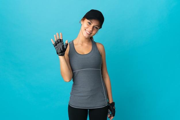 Подростковая спортивная русская девушка изолирована на синем фоне, салютуя рукой с счастливым выражением лица