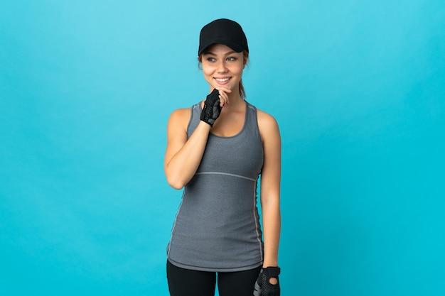 横を見て笑っている青い壁に分離されたティーンエイジャーのスポーツロシアの女の子