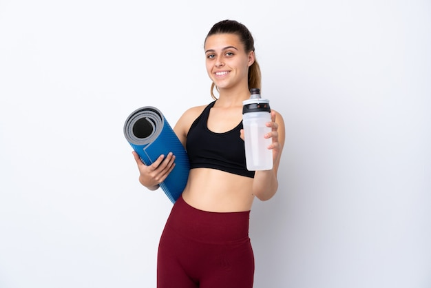 Teenager sport woman over isolated white wall with sports water bottle and with a mat