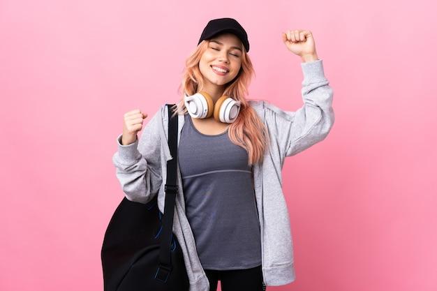 Подростковая спортивная женщина со спортивной сумкой на изолированном фоне празднует победу