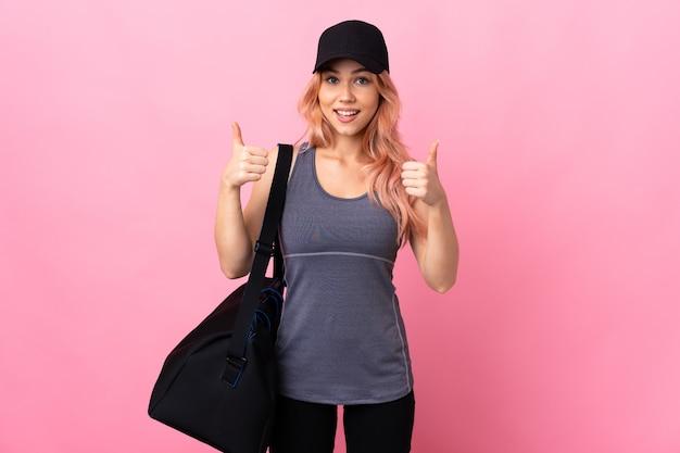 제스처를 엄지 손가락을주는 고립 된 벽 위에 스포츠 가방을 가진 십 대 스포츠 여자