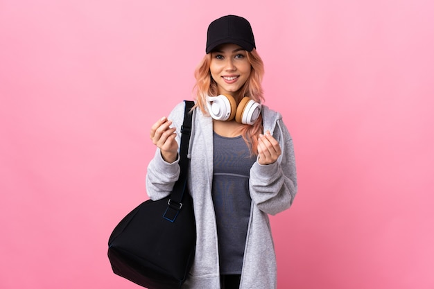 お金のジェスチャーを作る孤立した壁の上のスポーツバッグを持つティーンエイジャーのスポーツ女性