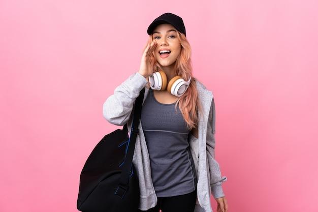 Подростковая спортивная женщина со спортивной сумкой над изолированной стеной и кричит с широко открытым ртом