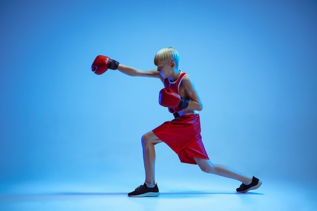 Teenager in sportswear boxing isolated on blue studio background in neon light. novice male caucasian boxer training hard and working out, kicking. sport, healthy lifestyle, movement concept.