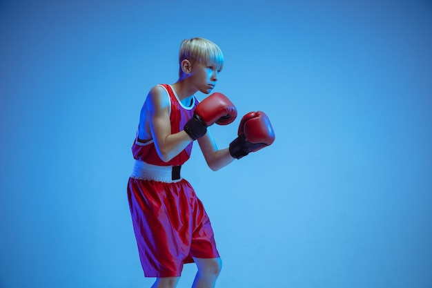 Teenager in sportswear boxing isolated on blue studio wall