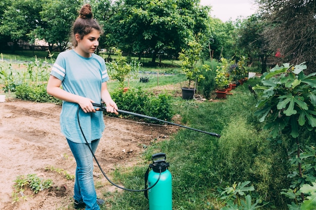 Teenager spraying plants in garden
