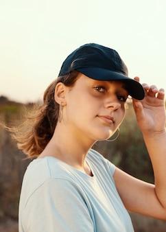 해질녘 들판에 서서 카메라를 똑바로 바라보는 10대. 티셔츠와 짙은 파란색 야구 모자를 쓰고 바이저를 만지는 십대 소녀. 모자와 티셔츠 모형