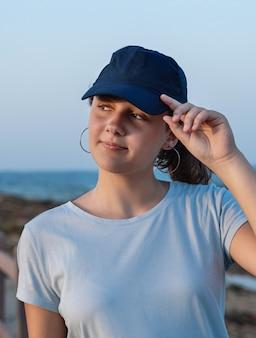 日没時に海のそばに立っているティーンエイジャー。 tシャツと紺色の野球帽をかぶってバイザーに触れている10代の少女。キャップとtシャツのモックアップ