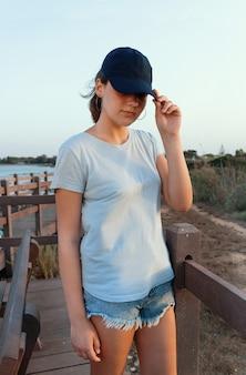해질녘 바다 옆에 서 있는 10대. 티셔츠와 짙은 파란색 야구 모자를 쓰고 바이저를 만지는 십대 소녀. 그늘에서 얼굴. 모자와 티셔츠 모형