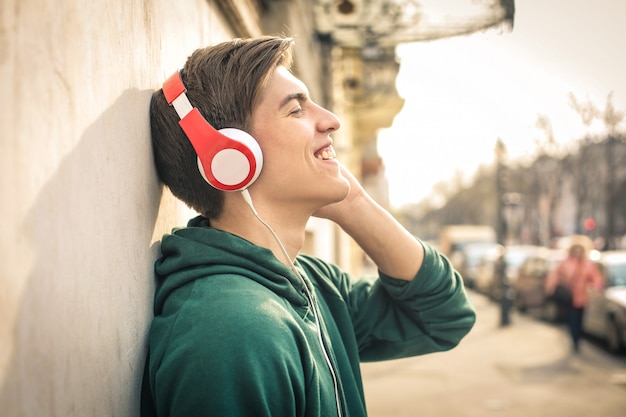 Teenager standing in the street, listening music with headphones