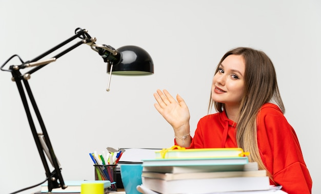 Teenager student girl in her room saluting with hand with happy expression