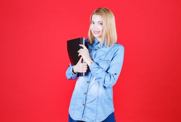 黒いドキュメントフォルダを保持し、孤立した赤い壁で笑っているティーンエイジャーの学生の女の子
