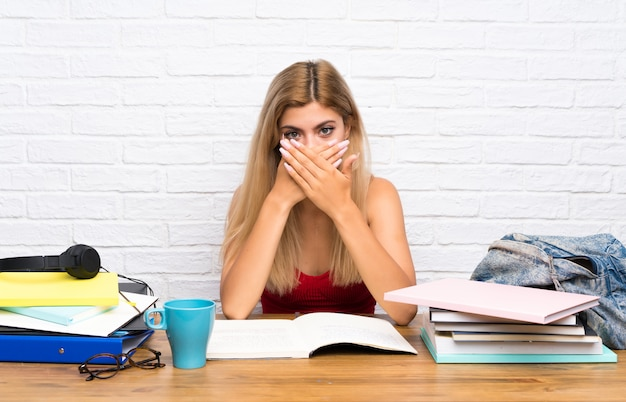 Teenager student girl at indoors covering mouth with hands