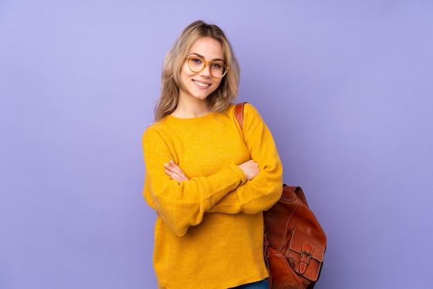 Девушка студента подростка на пурпуре с стеклами и усмехаться