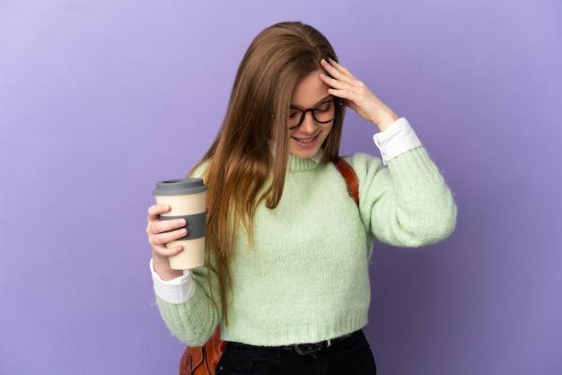 Девушка студента подростка над изолированным фиолетовым фоном смеясь