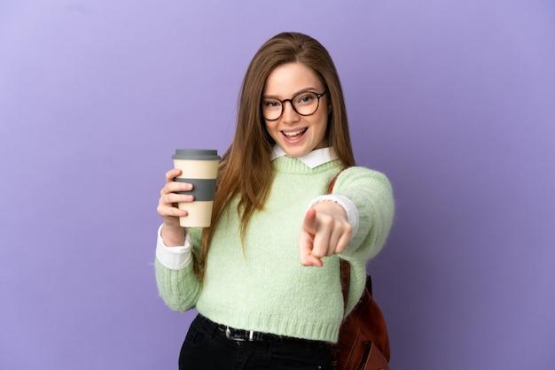 Девушка-подросток студент на изолированном фиолетовом фоне удивлен и указывает фронт