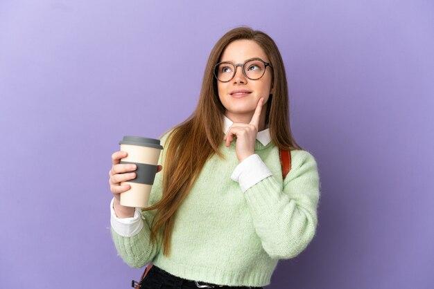 Девушка-подросток студент на изолированном фиолетовом фоне думает об идее, глядя вверх