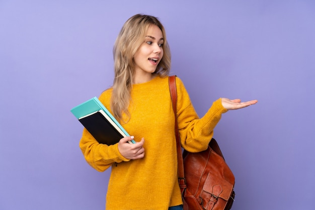 Teenager student girl on purple holding copyspace with two hands
