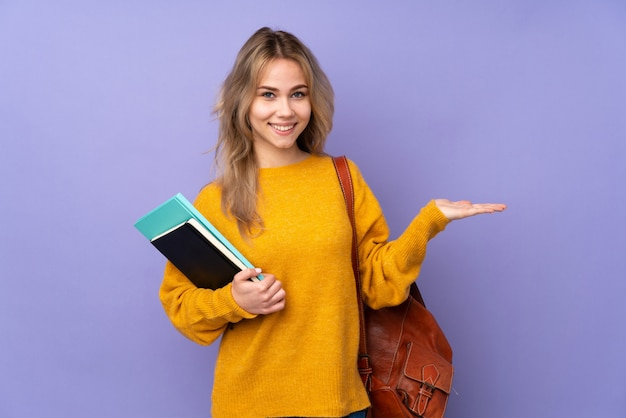 Teenager student girl on purple holding imaginary on the palm to insert an ad