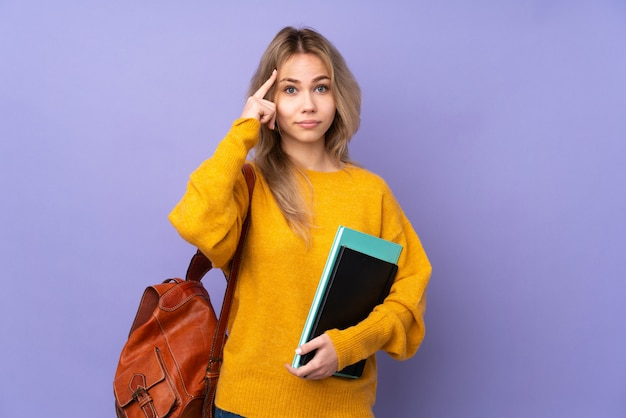 Teenager student girl on purple wall thinking an idea