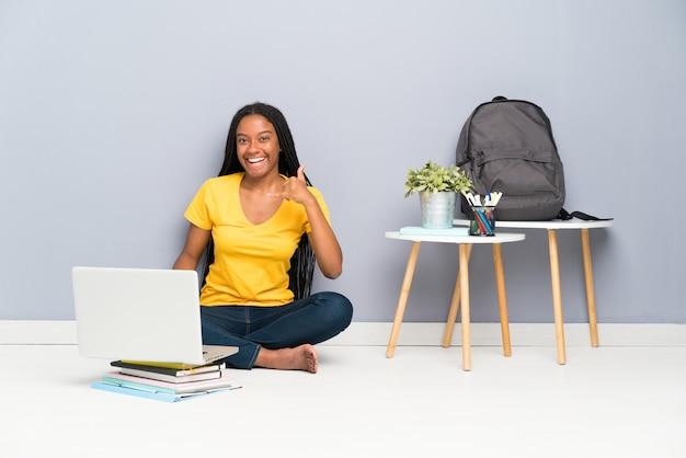 Teenager student girl sitting on the floor making phone gesture