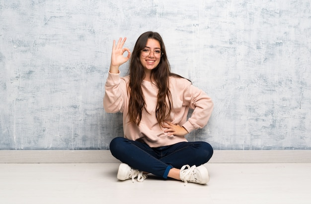 Teenager student girl studying in a table showing ok sign with fingers