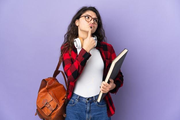Студент-подросток, изолированные на фиолетовом фоне, сомневаясь, глядя вверх