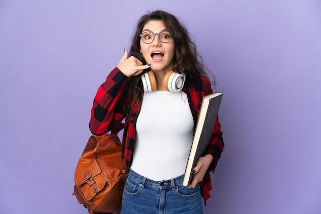 Студент-подросток, изолированные на фиолетовом фоне, делая телефонный жест. перезвони мне знак
