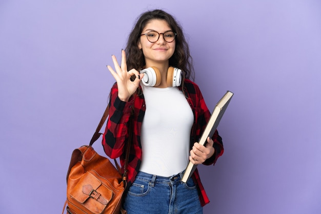Студент-подросток изолирован на фиолетовом фоне, показывая знак ок пальцами