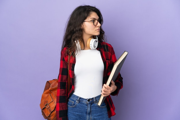 Teenager student isolated on purple background looking to the side
