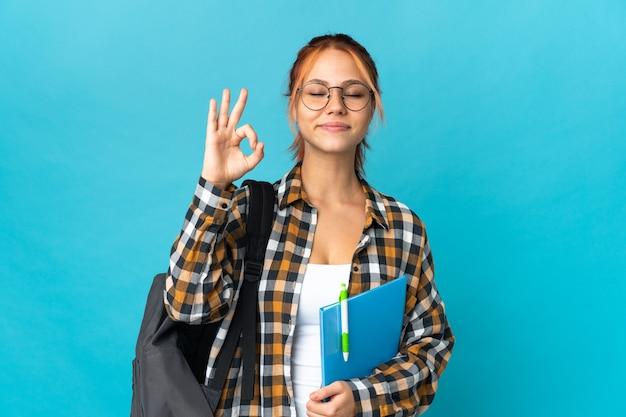 Студент-подросток русская девушка изолирована на синей стене в позе дзен