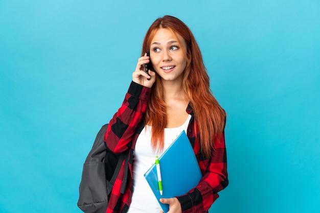Студент-подросток русская девушка изолирована на синей стене, разговаривая с кем-то по мобильному телефону