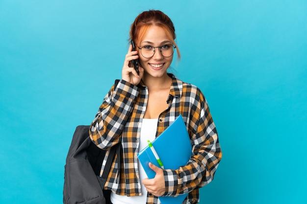 누군가와 휴대 전화로 대화를 유지하는 파란색 벽에 고립 된 십 대 학생 러시아 소녀