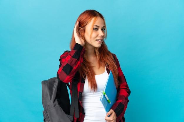 귀에 손을 넣어 뭔가를 듣고 파란색 벽에 고립 된 십 대 학생 러시아 소녀