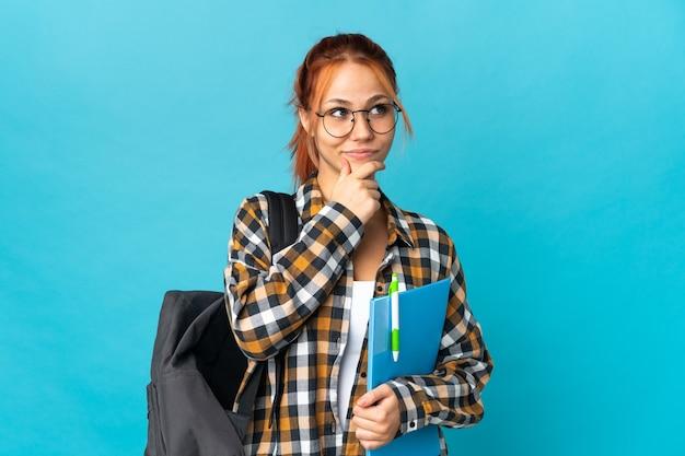 찾는 동안 아이디어를 생각하는 파란색 벽에 고립 된 십 대 학생 러시아 소녀
