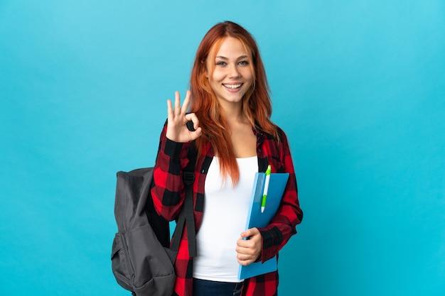 Русская девушка студент-подросток на синем показывает знак ок двумя руками