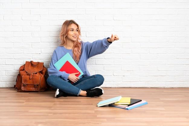 ピンクの髪の10代の学生女性が屋内で床に座って親指を立てるジェスチャーを与える