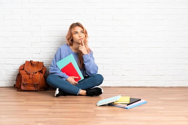 ピンクの髪の10代の学生女性が見上げている間疑問を持って屋内で床に座っている