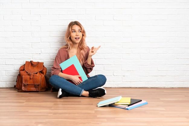 손가락을 들어 올리는 동안 솔루션을 실현하려는 실내에서 바닥에 앉아 분홍색 머리를 가진 십 대 학생 여자