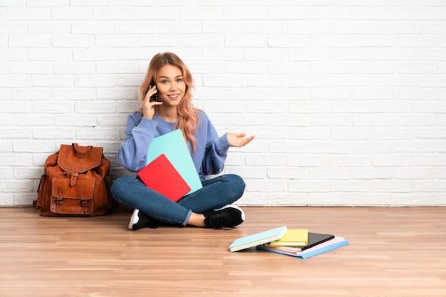 誰かと携帯電話と会話をしながら屋内の床に座っているピンクの髪の10代の学生女性