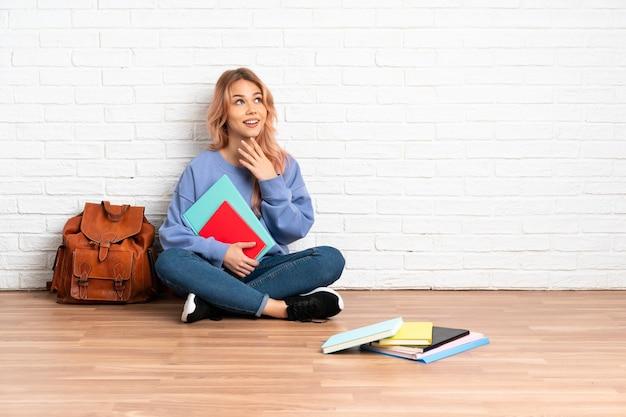 ピンクの髪の10代の学生女性が笑顔で見上げる屋内で床に座っている
