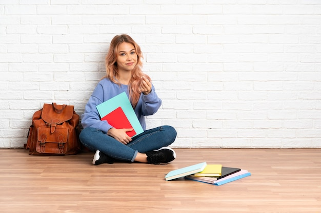 Студент-подросток женщина с розовыми волосами сидит на полу в помещении, делая денежный жест