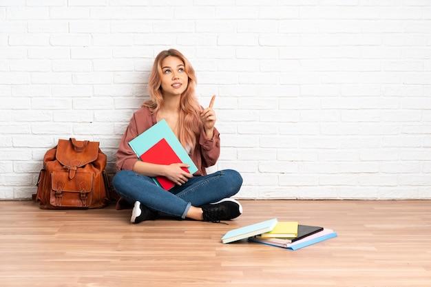 좋은 아이디어를 가리키는 실내에서 바닥에 앉아 분홍색 머리를 가진 십 대 학생 여자